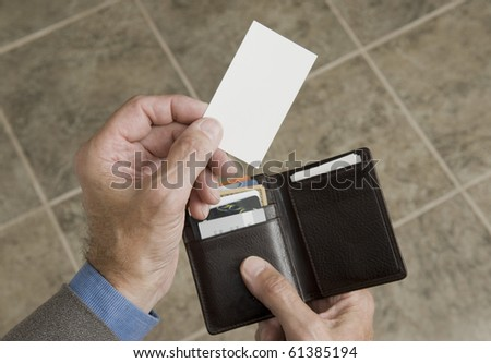man holding his wallet and extending a blank business card