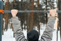 Man holding horizontal bar outside in winter. Human pulls up on sports equipment. Winter workout