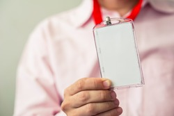 Man holding Identification white blank plastic id card.