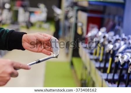 Man holding in hand golf club at a Golf Shop. Closeup photo