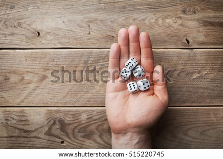 Man holding in hand white dice over the wooden table from above. Gambling devices. Game of chance concept. #515220745