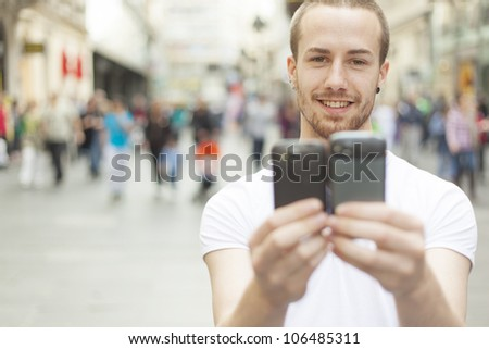 Man holding in hands two mobile phone, blurred city street and people in background