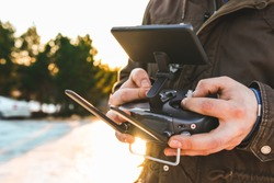 Man holding in his hands remote controller joystick transmitter flying the drone with sun shining bright day outdoors