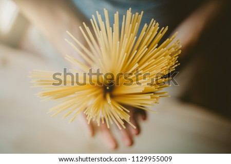 Man holding italian uncooked spaghetti, ready to cook. Closeup. Italian food or cooking concept. Selective focus