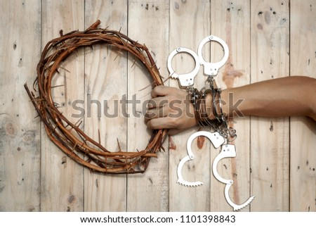 Man Holding Jesus Crown Thorns with His Hand and Many Handcuffs. Concept Picture of a Trapped Man Who Need Help by Jesus the Savior.