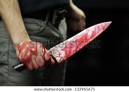 Man holding knife with blood dripping