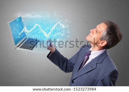 Man holding laptop projecting financial information, diagrams and charts