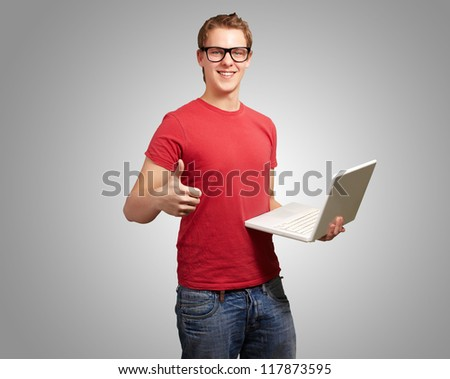 Man holding laptop with thumbs up