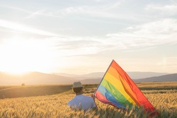 man holding LGBT gay rainbow flag in beautiful sunset landscape.concept of loneliness and sadness for cancellation of gay pride by coronavirus pandemic