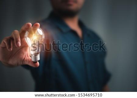 man holding light bulbs, ideas of new ideas with innovative technology and creativity.