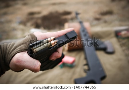 Man holding loaded magazine with 7.62 bullets (ammo) in his hand waiting to reload russian rifle SKS in modern tuning (black plastic body) with green canvas on the background on sand field #1407744365
