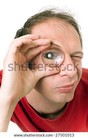 man holding magnifying lens on right eye and looking camera