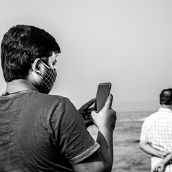 Man Holding mobile phone and clicking pictures and/or reading something