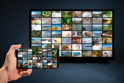man holding mobile phone with many icons of video service on demand on background Oline TV VOD provider. Interface of video distribution service. Subscription Streaming video. Media TV on demand