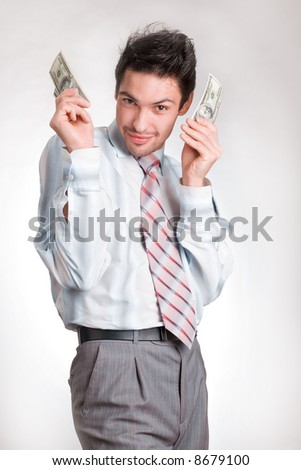 Man Holding Money. man in a white shirt and a red tie on a white background. The businessman holds money in hands. Hands are lifted upwards and pressed to the person. Dollars are developed by a fan
