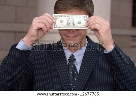 Man holding one dollar bill in front of his eyes