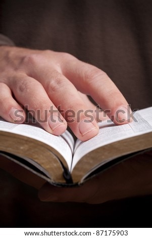 Man holding open Bible in his hands.