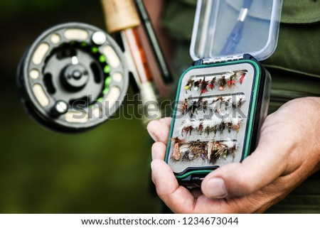 Man holding open box of flies for fly fishing in hand. Fish rod blured in background.