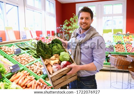 Man holding organic vegetables in a wooden box in grocery store
