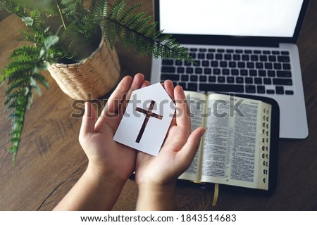 Man holding paper church icon praying by faith with computer laptop, Church services online concept, Online church at home concept, spirituality and religion.