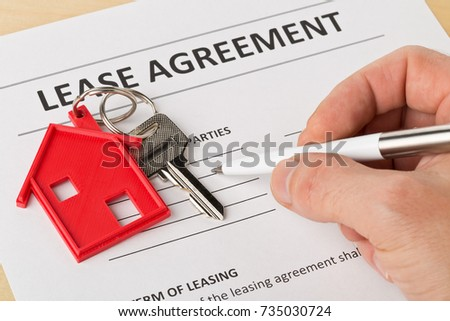 Man holding pen over house door key with red keychain pendant and lease agreement form on wooden desk - house or apartment rental concept Imagine de stoc ©