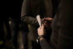Man holding perfume blotters in his hand. Preparing to test perfumes. Perfume workshop concept.
