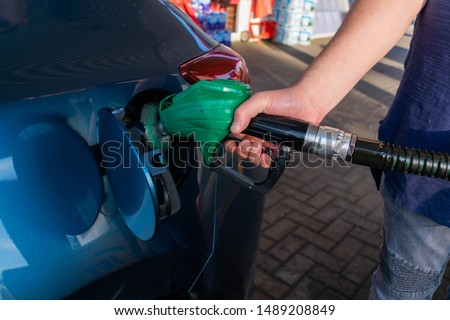 Man holding petrol nozzle pump filling up blue car at a gas station with fuel such as petrol or diesel. Rising prices of gas and fuel concept. Pollution, reliance, industry concepts or background