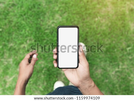 man holding phone showing blank screen walking on lawn