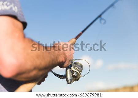 Man holding pole while fishing under a blue sky. #639679981