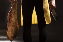 Man holding pork leg and kitchen ax on black background.