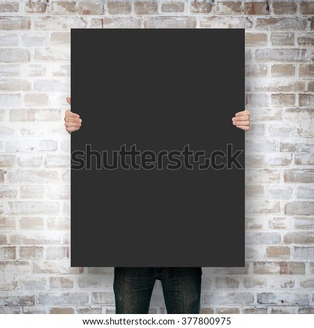 Man holding poster mockup over brick wall #377800975