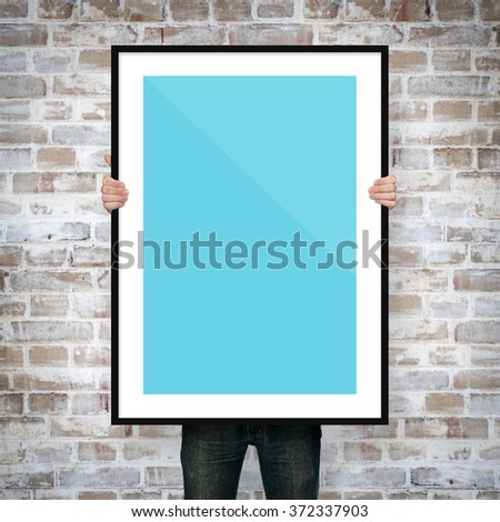 man holding poster mockup with frame on brick background #372337903