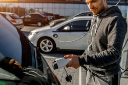 Man Holding Power Charging Cable For Electric Car In Outdoor Car Park. And he s going to connect the car to the charging station in the parking lot near the shopping center
