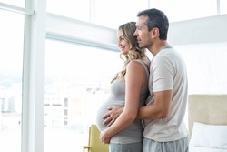 Man holding pregnant womans stomach in bedroom