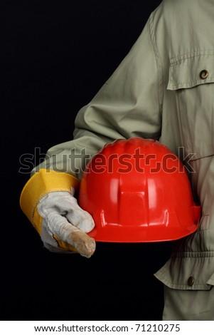 man holding red helmet over black background