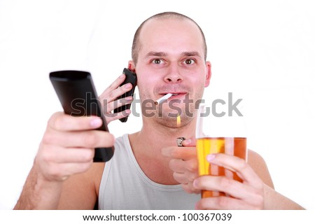 Man holding remote control, cigarette, cell phone and beer enjoying watching television