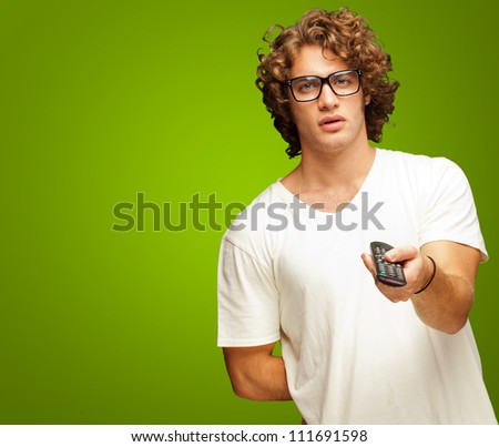 Man Holding Remote Control Isolated On Green Background