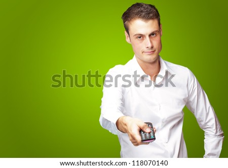 Man Holding Remote In His Hand On Green Background