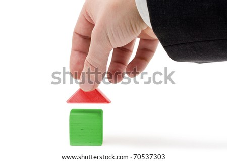 Man holding roof of toy house - real estate concept