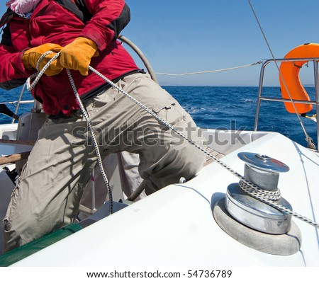 Man holding rope on sailing boat