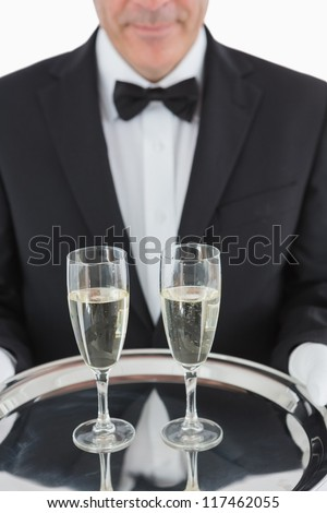 Man holding silver tray with three champagne flutes