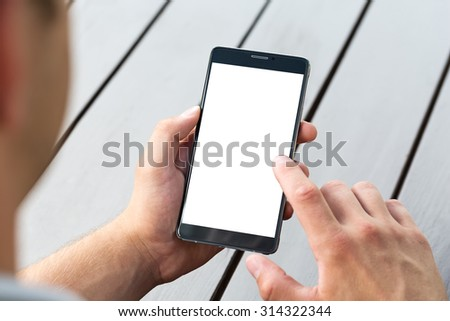 Man holding smart mobile phone on wooden table background #314322344