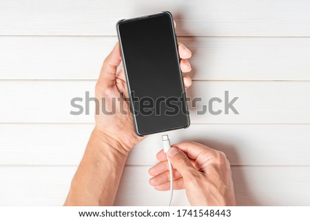 Man holding smart phone by connecting charger. Cellphone with blank screen in hands and charger on white background Foto stock ©