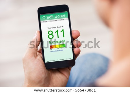 Man Holding Smart Phone Showing Credit Score Application On A Screen #566473861