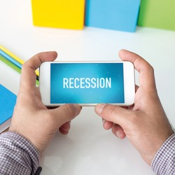 Man holding smartphone which displaying Recession