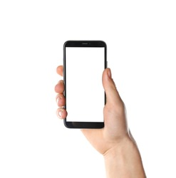 Man holding smartphone with blank screen on white background, closeup of hand. Space for text