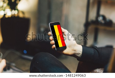 Man holding Smartphone with Flag of Belgium. Belgium Flag on Mobile Screen. #1481249063