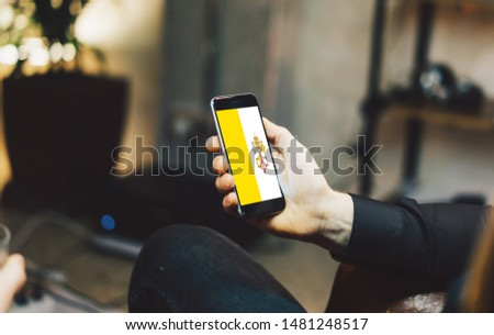 Man holding Smartphone with Flag of Holy See. Holy See Flag on Mobile Screen.