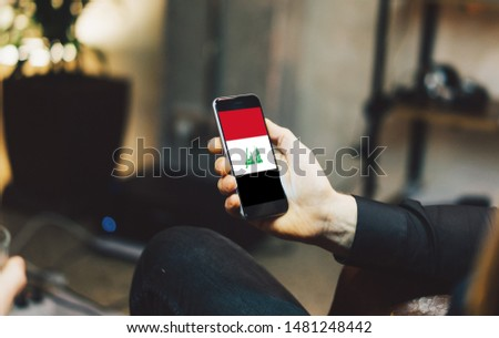 Man holding Smartphone with Flag of Iraq. Iraq Flag on Mobile Screen.