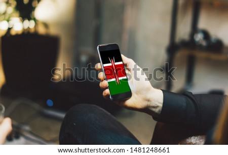 Man holding Smartphone with Flag of Kenya. Kenya Flag on Mobile Screen.